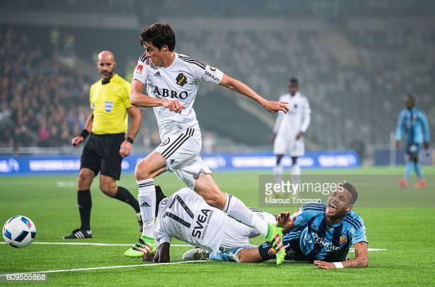 Mathias Ranegie of Djurgardens IF falls behind Ebenezer Ofori of AIK and Sauli Vaisanen of AIK during the Allsvenskan match between Djurgardens IF...