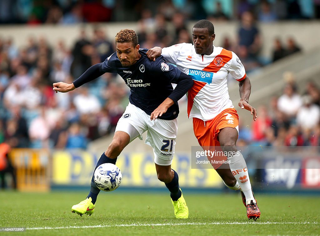 Mathias Ranegie of Millwall tackles with Donervon Daniels of Blackpool during the Sky Bet Championship match between Millwall and Blackpool at The Den on August 30, 2014 in London, England.