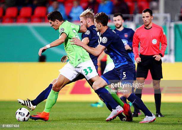 Mathias Wittek and Sebastian Griesbeck of Heidenheim and Mario Gomez of Wolfsburg battle for the ball during the DFB Cup second round match between 1...
