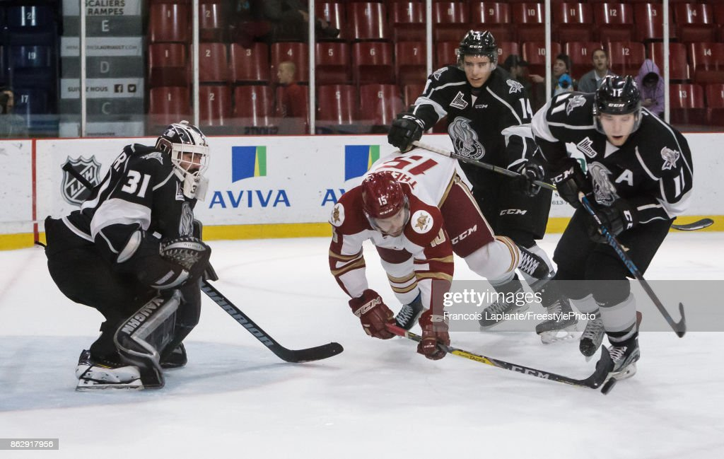 Mathieu Bellemare #31 of the Gatineau Olympiques guards his net as Vitalii Abramov #11 defends against Dawson Theede #15 of the Acadie-Bathurst Titan who falls onto the ice as he reaches for the rebound on October 18, 2017 at Robert Guertin Arena in Gatineau, Quebec, Canada.