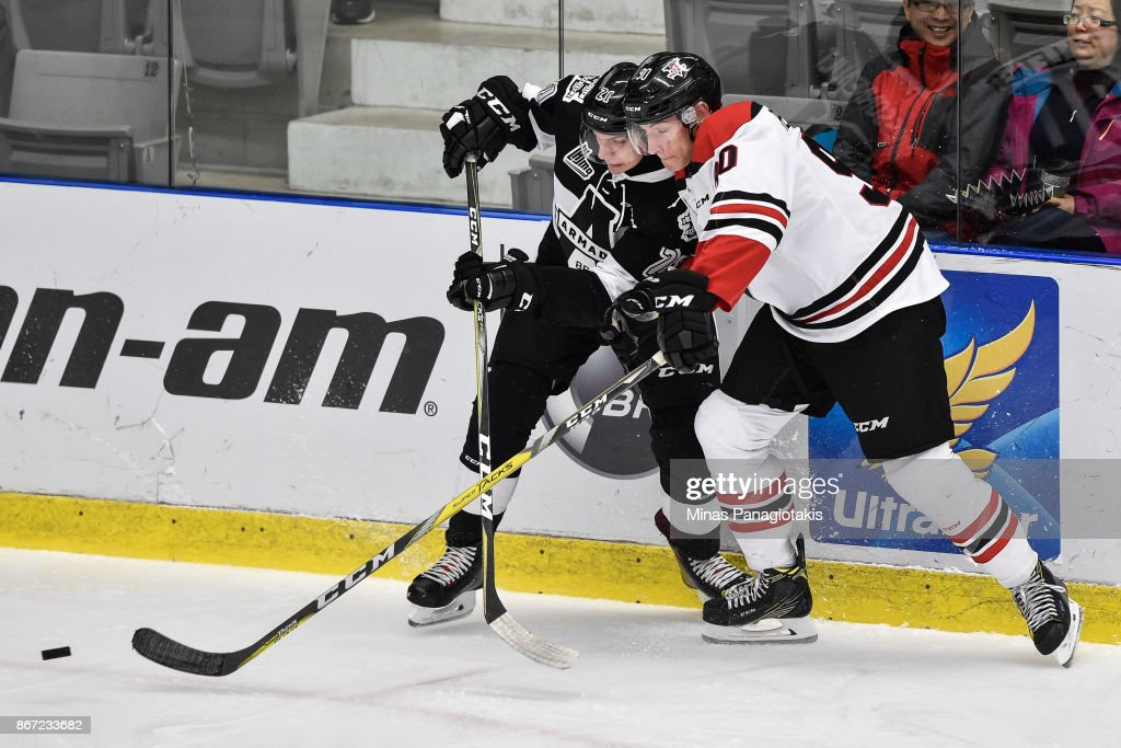 Mathieu Boissonneault #21 of the Blainville-Boisbriand Armada and Thomas Pelletier #90 of the Drummondville Voltigeurs battle for the puck during the QMJHL game at Centre d'Excellence Sports Rousseau on October 27, 2017 in Boisbriand, Quebec, Canada.
