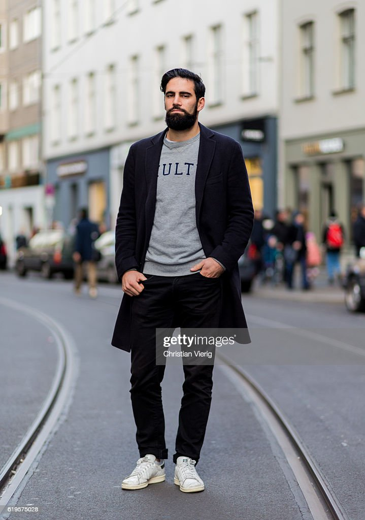 Mathieu Caudal wears a black wool coat, grey sweater, black pants, white sneaker on October 31, 2016 in Berlin, Germany.