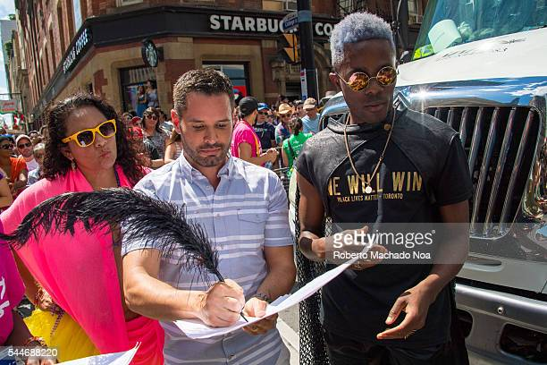 Mathieu Chantelois Pride Toronto's executive director signs in acceptance a list of demands from the Black Lives Matter Toronto movement as they...