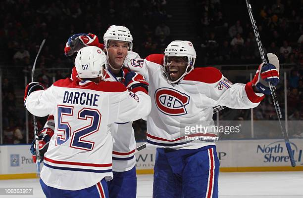 Mathieu Darche Benoit Poulin and PK Subban of the Montreal Canadiens celebrate Poulin's game winning goal against the New York Islanders at the...