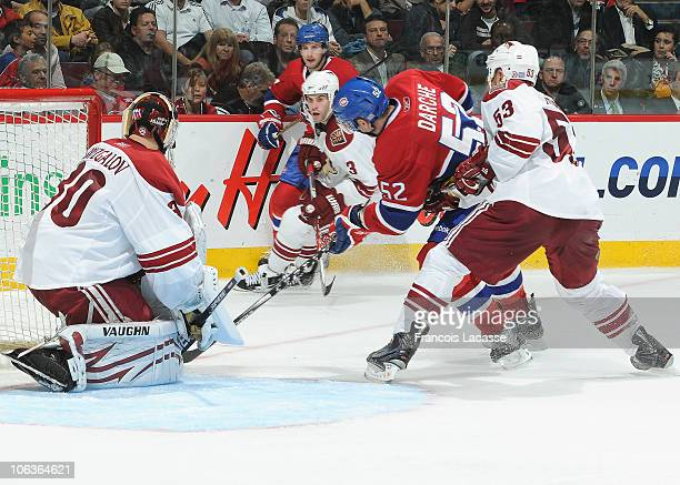 Mathieu Darche of the Montreal Canadiens attempts to get the puck past goalie Ilya Bryzgalov and Derek Morris of the Phoenix Coyotes during the NHL...