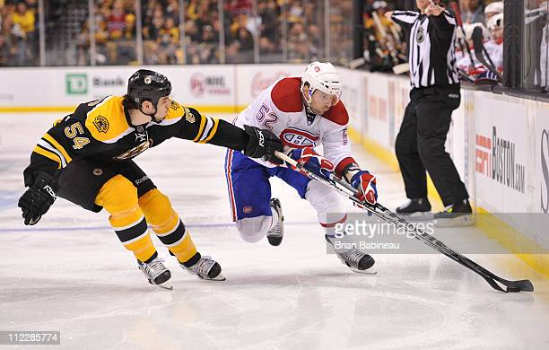 Mathieu Darche of the Montreal Canadiens fights for the puck against Adam McQuaid of the Boston Bruins in Game Two of the Eastern Conference...