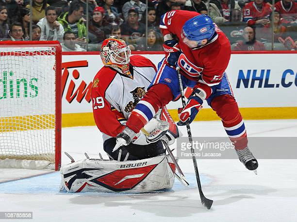 Mathieu Darche of the Montreal Canadiens jumps away front a shot in front of goaltender Tomas Vokoun of the Florida Panthers during the NHL game on...
