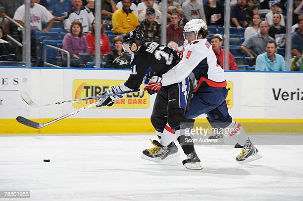 Mathieu Darche of the Tampa Bay Lightning battles against Alexander Ovechkin of the Washington Capitals for control of the puck at St Pete Times...