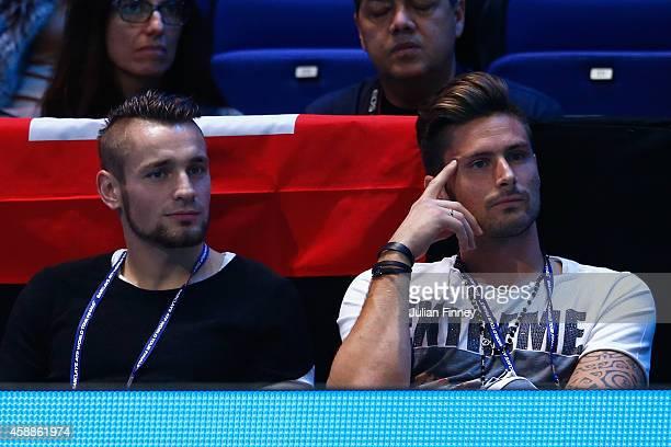 Mathieu Debuchy and Olivier Giroud of Arsenal watch Novak Djokovic of Serbia compete in the round robin singles match against Stan Wawrinka of...