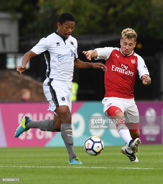 Mathieu Debuchy of Arsenal challenges Angelo Balenta of Boreham Wood during the match between Boreham Wood and Arsenal XI at Meadow Park on July 27...