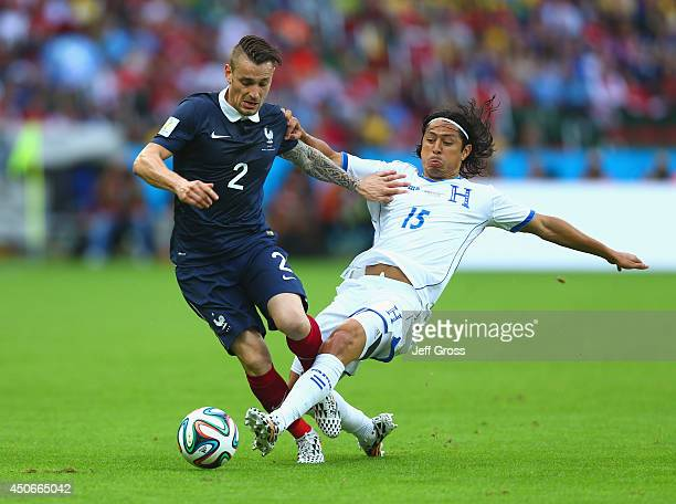 Mathieu Debuchy of France holds off a challenge by Roger Espinoza of Honduras during the 2014 FIFA World Cup Brazil Group E match between France and...