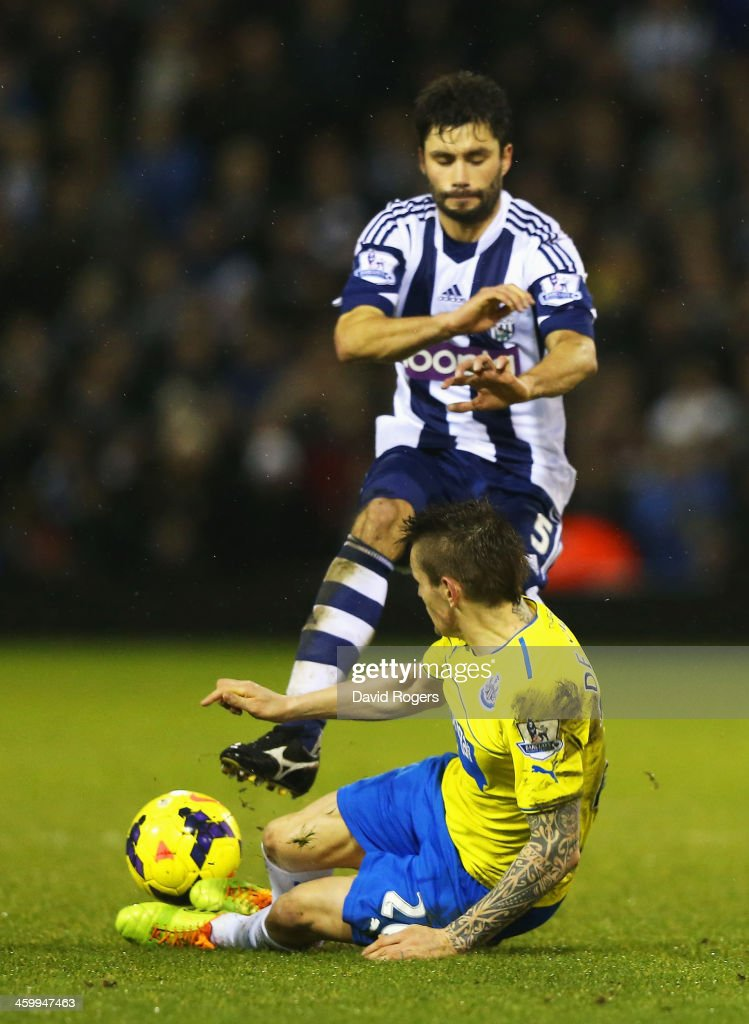 Mathieu Debuchy of Newcastle United challenges Claudio Yacob of West Bromwich Albion, a tackle leading to his sending off during the Barclays Premier League match between West Bromwich Albion and Newcastle United at The Hawthorns on January 1, 2014 in West Bromwich, England.