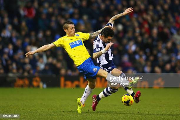 Mathieu Debuchy of Newcastle United tackles Liam Ridgewell of West Bromwich Albion during the Barclays Premier League match between West Bromwich...