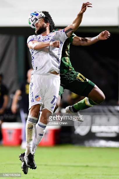 Mathieu Deplagne of FC Cincinnati and Jeremy Ebobisse of Portland Timbers jump to head the ball during a round of sixteen match in the MLS Is Back...