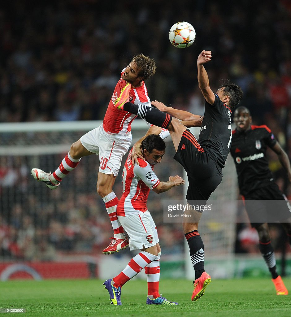 Mathieu Flamini and Santi Cazorla of Arsenal challenge Mustafa Pektemek of Besiktas during the UEFA Champions League Qualifing match between Arsenal and Besiktas at Emirates Stadium on August 27, 2014 in London, United Kingdom.
