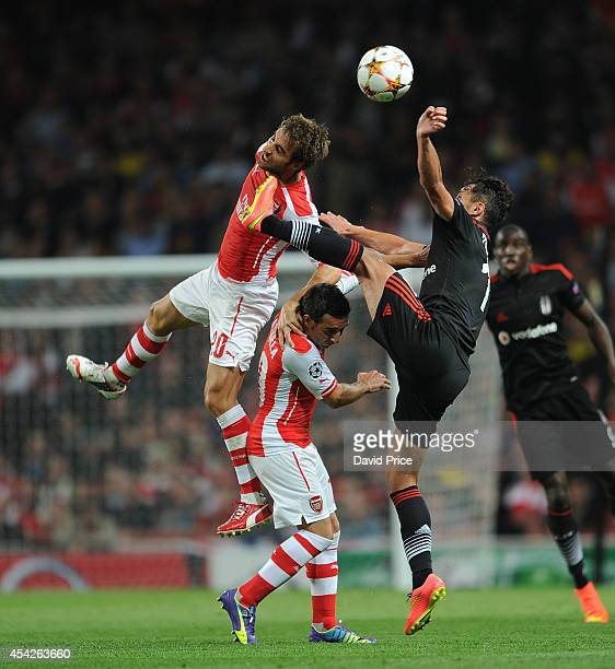 Mathieu Flamini and Santi Cazorla of Arsenal challenge Mustafa Pektemek of Besiktas during the UEFA Champions League Qualifing match between Arsenal...