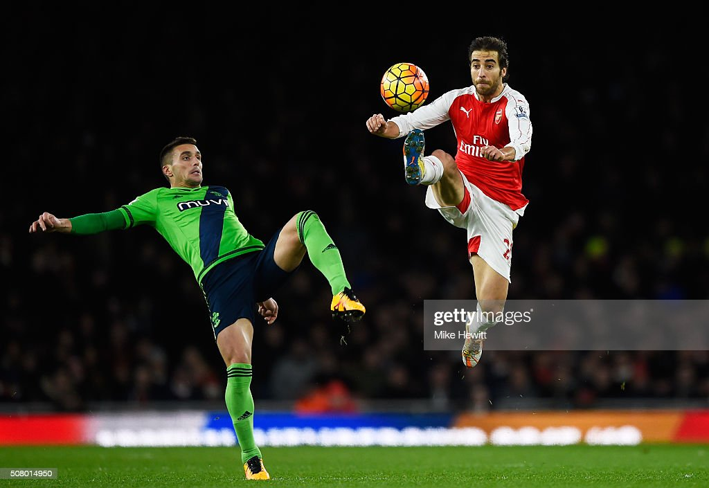 Mathieu Flamini of Arsenal and Dusan Tadic of Southampton compete for the ball during the Barclays Premier League match between Arsenal and Southampton at the Emirates Stadium on February 2, 2016 in London, England.