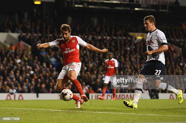 Mathieu Flamini of Arsenal scores their first goal as Kevin Wimmer of Tottenham Hotspur looks on during the Capital One Cup third round match between...