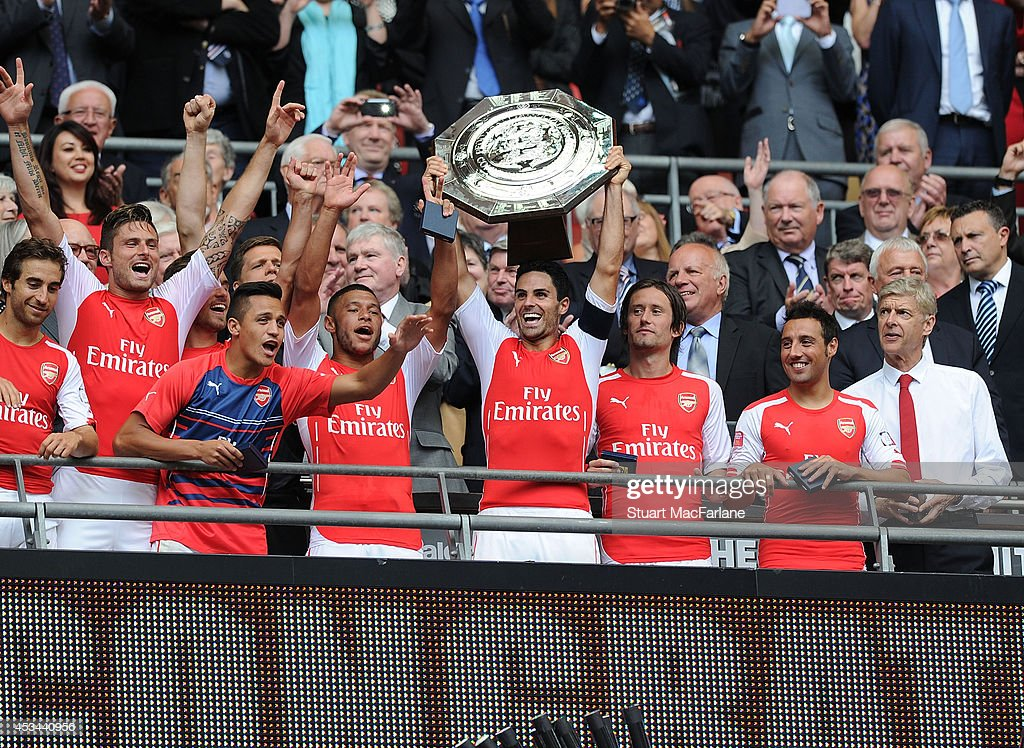 Mathieu Flamini, Olivier Giroud, Alexis Sanchez, Alex Oxlade-Chamberlain, Mikel Arteta, Tomas Rosicky, Santi Cazorla and manager Arsene Wenger celebrate after the FA Community Shield match between Arsenal and Manchester City at Wembley Stadium on August 10, 2014 in London, England.
