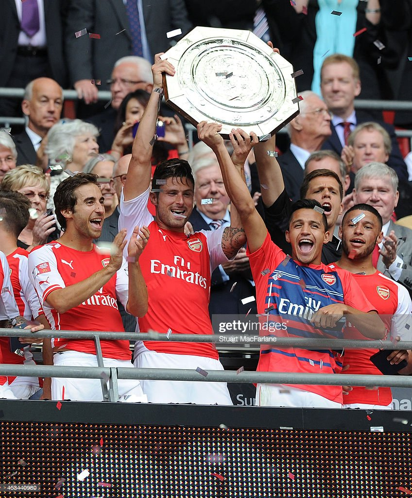 Mathieu Flamini, Olivier Giroud and Alexis Sanchez lift the Community Shield after the match between Arsenal and Manchester City at Wembley Stadium on August 10, 2014 in London, England.