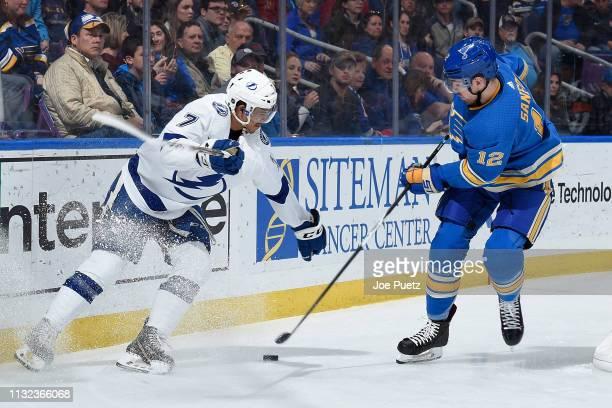 Mathieu Joseph of the Tampa Bay Lightning battles Zach Sanford of the St. Louis Blues for the puck at Enterprise Center on March 23, 2019 in St....
