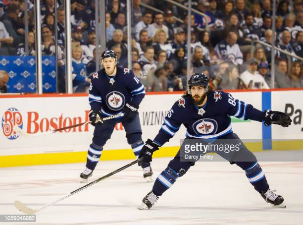 Mathieu Perreault and Bryan Little of the Winnipeg Jets keep an eye on the play during second period action against the St Louis Blues at the Bell...