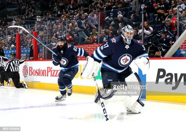 Mathieu Perreault and goaltender Connor Hellebuyck of the Winnipeg Jets hit the ice prior to puck drop against the Chicago Blackhawks at the Bell MTS...