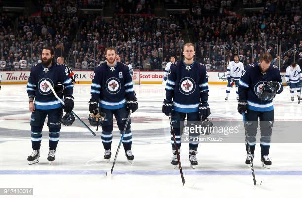 Mathieu Perreault Bryan Little Nikolaj Ehlers and Toby Enstrom of the Winnipeg Jets stand on the ice during the singing of the National anthems prior...