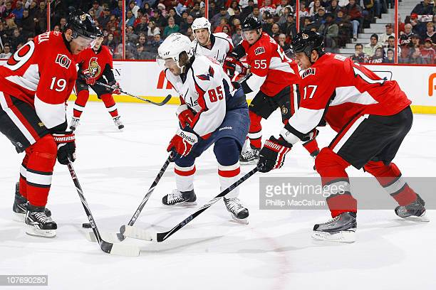 Mathieu Perreault of the Washington Capitals steals the puck away from Jason Spezza and Filip Kuba of the Ottawa Senators in a game at Scotiabank...