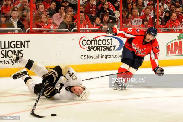 Mathieu Perreault of the Washington Capitals trips Paul Martin of the Pittsburgh Penguins during the third period of a NHL hockey game on February 6...