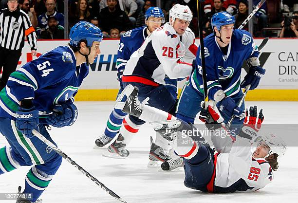 Mathieu Perreault of the Washington Capitals tumbles while Aaron Volpatti and Dale Weise of the Vancouver Canucks and Matt Hendricks of the Capitals...
