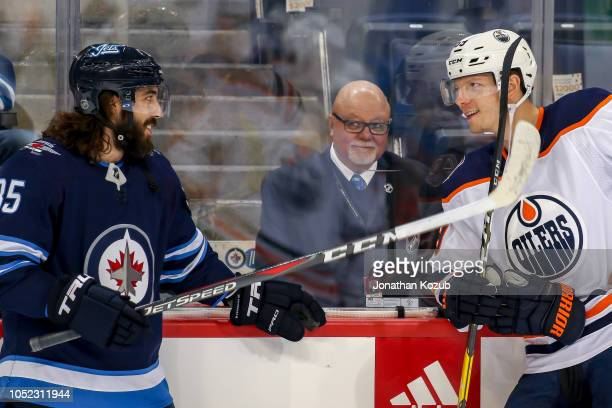 Mathieu Perreault of the Winnipeg Jets and Alex Chiasson of the Edmonton Oilers chat during the pregame warm up prior to NHL action at the Bell MTS...
