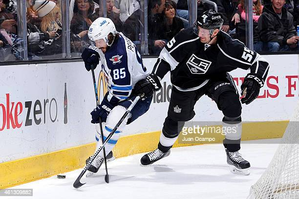 Mathieu Perreault of the Winnipeg Jets and Jeff Schultz of the Los Angeles Kings fight for possession of the puck during a game at STAPLES Center on...