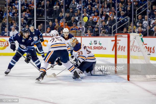 Mathieu Perreault of the Winnipeg Jets backhands the puck past goaltender Cam Talbot of the Edmonton Oilers for a first period goal at the Bell MTS...
