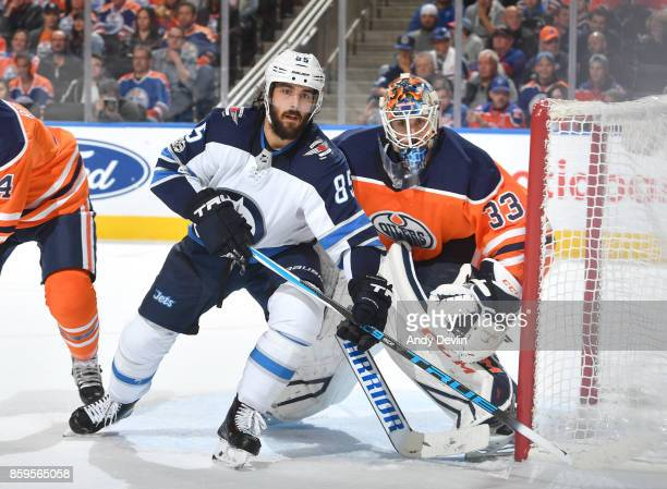 Mathieu Perreault of the Winnipeg Jets battles for position against Cam Talbot of the Edmonton Oilers on October 9 2017 at Rogers Place in Edmonton...