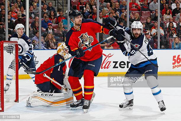 Mathieu Perreault of the Winnipeg Jets battles for position with Alex Petrovic in front of goaltender Roberto Luongo of the Florida Panthers at the...