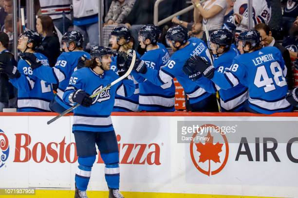 Mathieu Perreault of the Winnipeg Jets celebrates his third period goal against the Chicago Blackhawks with teammates at the bench at the Bell MTS...