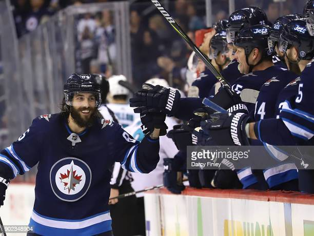 Mathieu Perreault of the Winnipeg Jets celebrates his third period empty net goal against the San Jose Sharks with teammates at the bench at the Bell...