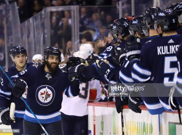 Mathieu Perreault of the Winnipeg Jets celebrates his third period goal against the Florida Panthers with teammates at the bench at the Bell MTS...