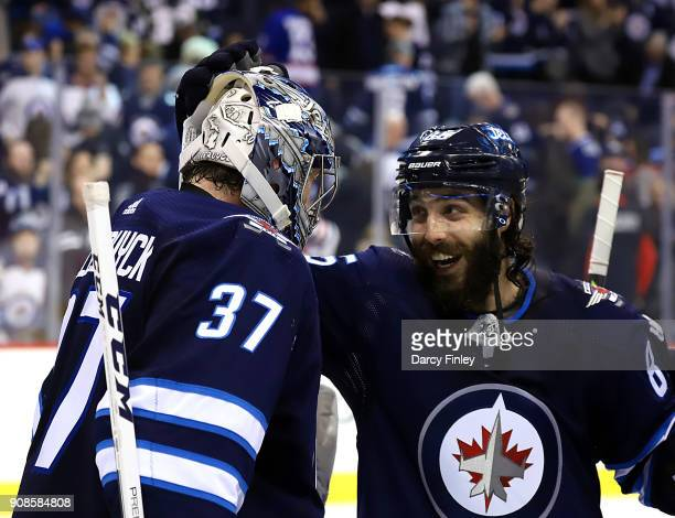 Mathieu Perreault of the Winnipeg Jets celebrates with goaltender Connor Hellebuyck following a 10 shutout victory over the Vancouver Canucks at the...