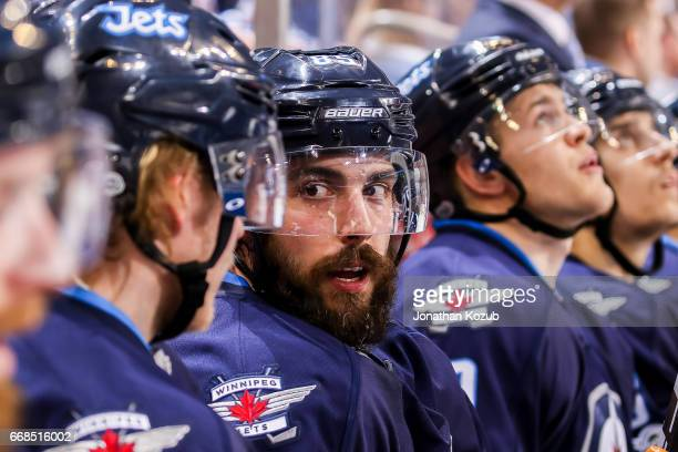 Mathieu Perreault of the Winnipeg Jets chats with a teammate on the bench during third period action against the Nashville Predators at the MTS...