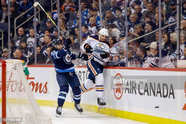 Mathieu Perreault of the Winnipeg Jets checks Jason Garrison of the Edmonton Oilers along the boards during first period action at the Bell MTS Place...