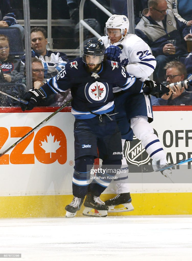 Mathieu Perreault #85 of the Winnipeg Jets checks Nikita Zaitsev #22 of the Toronto Maple Leafs into the boards during third period action at the Bell MTS Place on October 4, 2017 in Winnipeg, Manitoba, Canada.