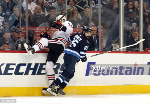 Mathieu Perreault of the Winnipeg Jets checks Victor Ejdsell of the Chicago Blackhawks along the boards during first period action at the Bell MTS...