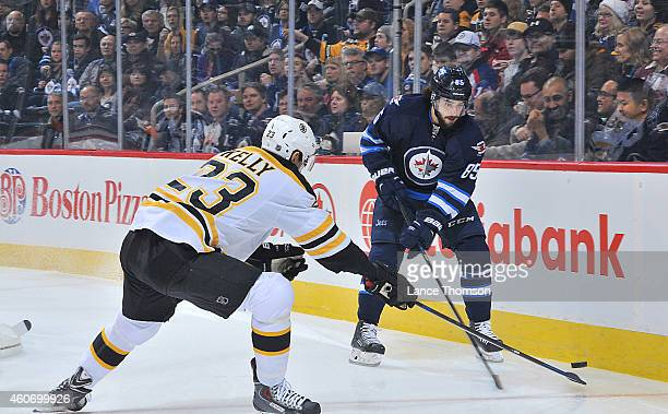 Mathieu Perreault of the Winnipeg Jets chips the puck over the stick of a defending Chris Kelly of the Boston Bruins during first period action on...