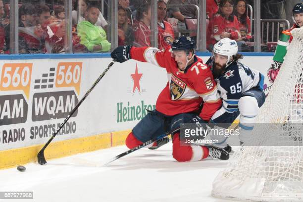 Mathieu Perreault of the Winnipeg Jets defends against Dryden Hunt of the Florida Panthers as he circles behind the net with the puck during first...