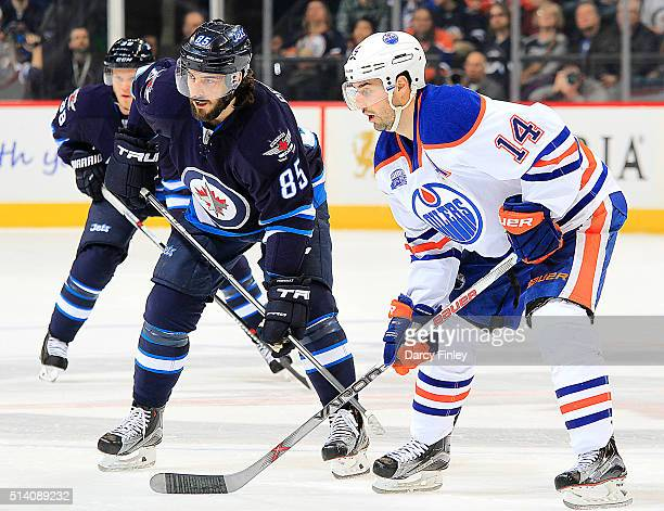 Mathieu Perreault of the Winnipeg Jets gets set against Jordan Eberle of the Edmonton Oilers during a first period faceoff at the MTS Centre on March...