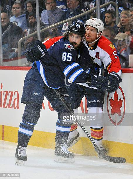 Mathieu Perreault of the Winnipeg Jets gets tangled up along the boards with Brian Campbell of the Florida Panthers during first period action on...