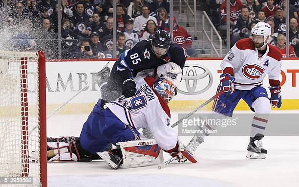 Mathieu Perreault of the Winnipeg Jets gets tied up with goaltender Mike Condon of the Montreal Canadiens in second period action in an NHL game at...