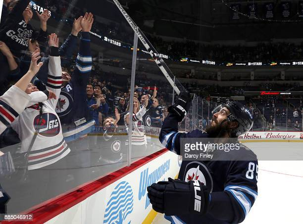 Mathieu Perreault of the Winnipeg Jets gives a souvenir stick to fans after receiving second star honors following a 50 victory over the Ottawa...